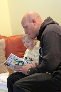 Assistant Soccer Coach James Wagenschutz reads to his son at the Children's Center.