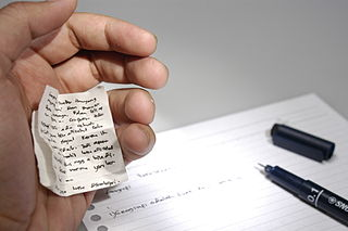 A small cheat sheet hidden in a hand over an examination paper.