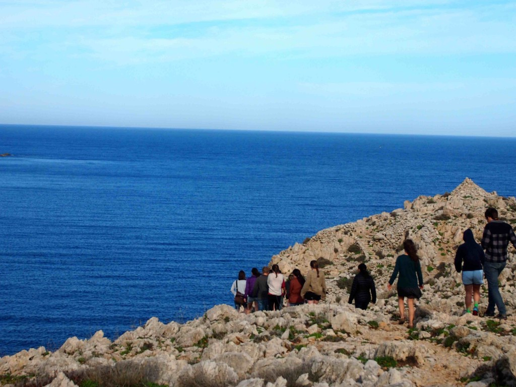 Students hike along the Mediterranean coast to the remains of a  prehistoric settlement situated atop a picturesque cliff