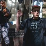 """DeAira Cooper '17, co-chair of CC's Black Student Union, uses a megaphone to lead the crowd in chants of """"Hands up, don't shoot"""" at protest held at the Earle Flagpole in early September. Many of the students, faculty, and staff joined Justin Haas '16, left, in raising their hands in protest of the events in Ferguson, Missouri. Photo by Esther Chan '16."""