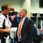 Joe Ellis '80, right, talks with Broncos quarterback Peyton Manning.
