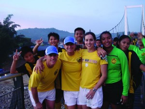 Three Colorado College alumni traveled to Malaysia this summer for the U.S.-Malaysia Women's Soccer Exchange. They coached soccer camps for girls, ran coaching clinics, and ran a training session for the Malaysian Women's National Soccer Team. This fall, they hosted a Malaysian contingency as they toured the U.S. Janine Szpara, Anna Shortt Thomas, and Karen Willoughby (all Class of '89, from left), stand on a bridge in Malaysia with their fellow athletes.