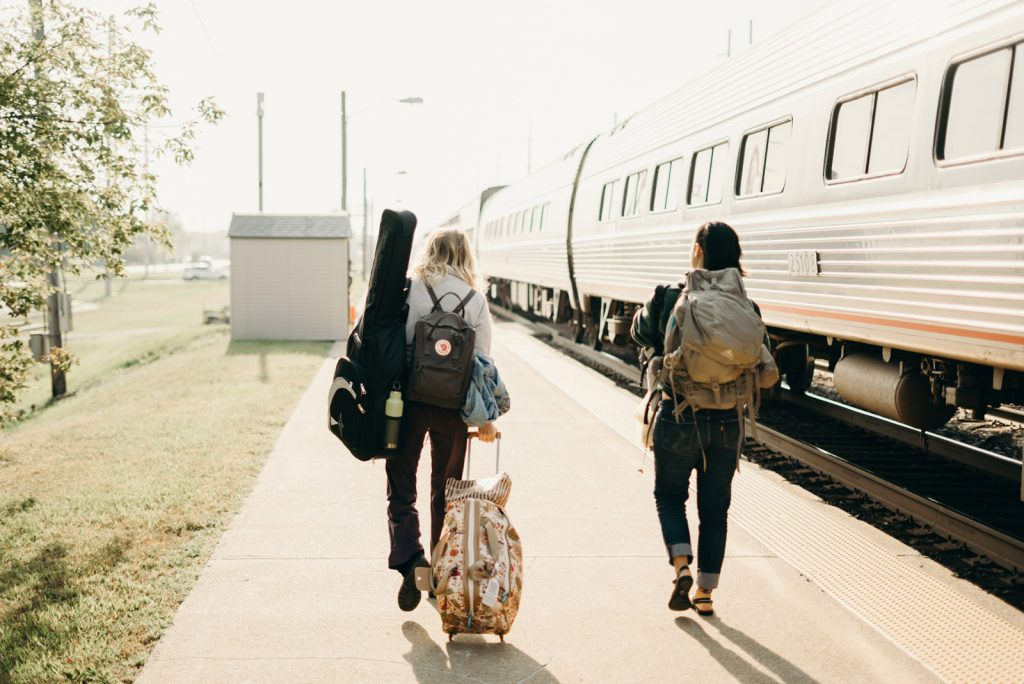 Two people walking down a train station platform