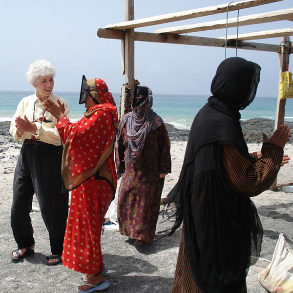 Sharon L. Smith, on an Omani beach, learns traditional songs from Beduin women. Photo courtesy of Sharon L. Smith '67.